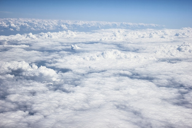 Heavy white / grey clouds from the view on a airplane, with blue sky and sunshine, a plane is flying above clouds