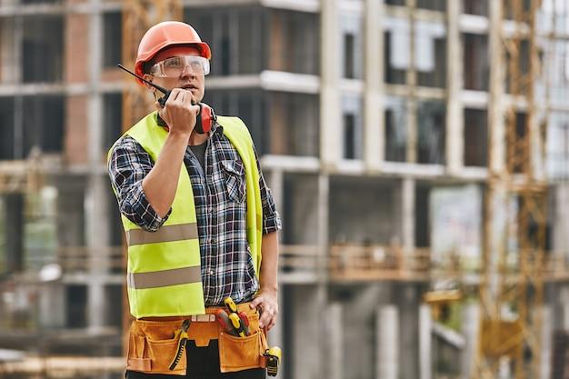 作業服と赤い保護ヘルメットで話しているヘッキング作業プロの若いビルダー