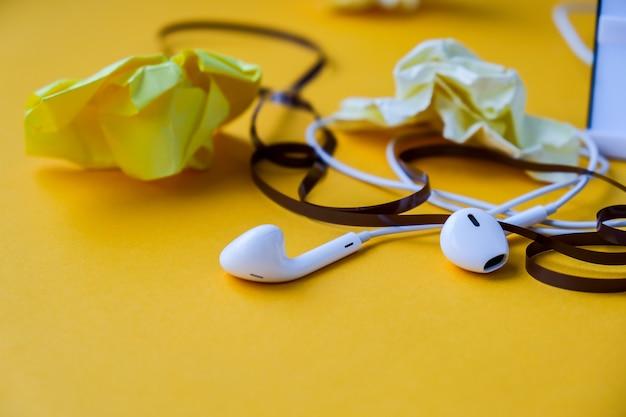 노란색 배경에 오디오 카세트 테이프와 구겨진 종이가 있는 헤드폰, 복사 공간. 팟캐스트 에피소드. 오디오북.