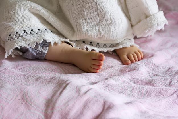 Пятка спящая девочка торчит из-под одеяла, селективный фокус