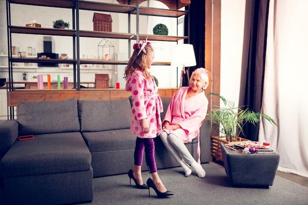 Каблуки бабушки. симпатичная забавная девчонка в халате впервые примеряет туфли красивой современной бабушки на высоких каблуках