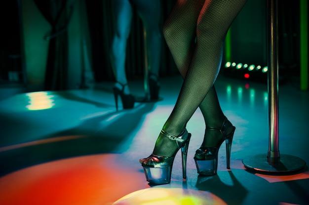Heels of sexy woman pole dancing or striptease. pylon in night club. stripper woman