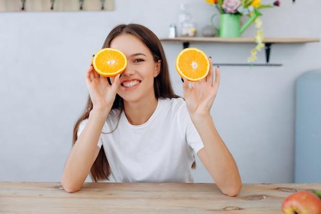 ◦ 두 개의 오렌지 조각이 있고 한쪽 눈을 감고있는 재미있는 재미있는 만화 긍정적 인 소녀.