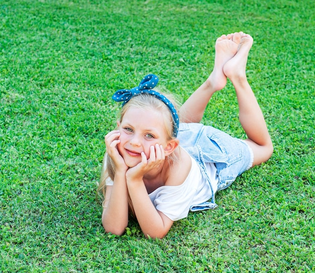 Ð¡heerful little girl in a denim jumpsuit, lying on a green grass