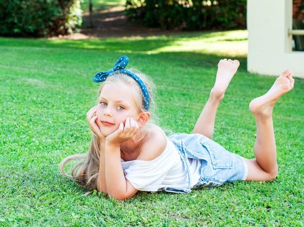緑の芝生の上に横たわって、デニムのジャンプスーツを着た陽気な少女