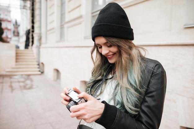 Сheerful woman wearing hat holding camera.