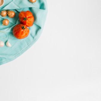 흰색 배경에 파란색 냅킨에 양파와 마늘 정향과 가보 토마토
