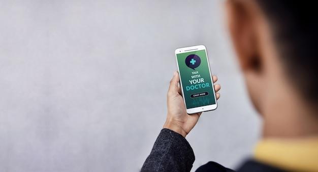Helathyライフスタイルとテクノロジーのコンセプト。現代のビジネスマンが携帯電話を介してオンライン医学アプリケーションを使用して彼の健康について医師に相談をリクエスト