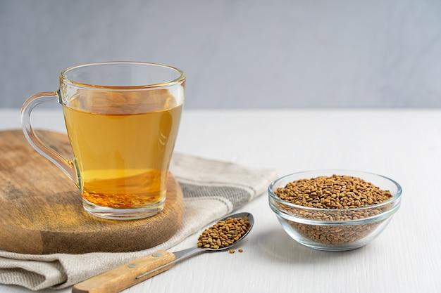 Золотой чайный напиток хельба из однолетнего растения пажитник, подается в стеклянной чашке с миской семян и спотом