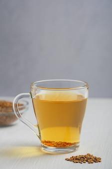 Золотой чайный напиток хельба из растения пажитник, подается в стеклянной чашке с семенами на белом деревянном столе