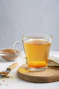 Хельба или золотой чай из семян однолетнего растения пажитник, подаваемый в стеклянной чашке с зернами в ложке