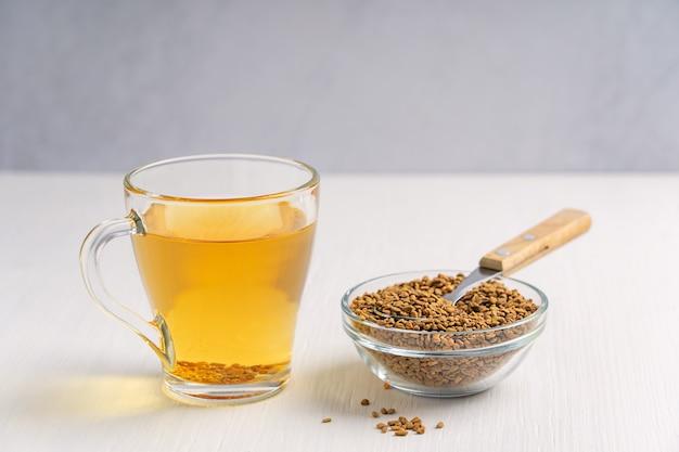 Хельба или золотой чай из однолетнего растения пажитник, подаваемый в стеклянной чашке с семенами и ложкой