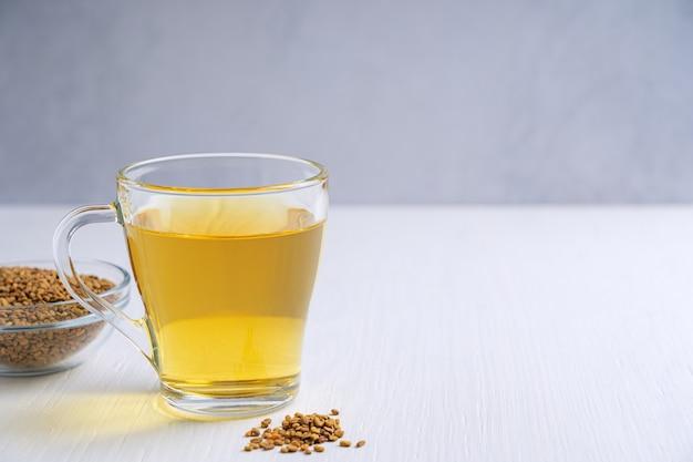 Хельба или золотой чай из пажитника, подаваемый в стеклянной чашке с миской семян на деревянном столе