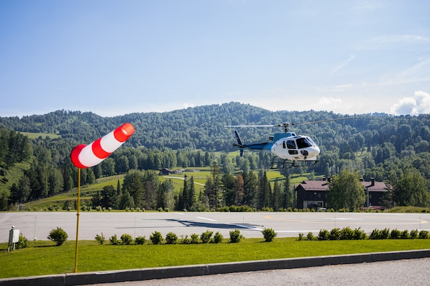 Helicopter among green mountains and hills
