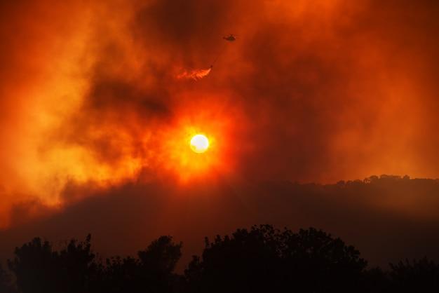 헬리콥터는 산불과 싸우고 붉은 하늘과 무거운 연기가 나는 일몰의 극적인 풍경