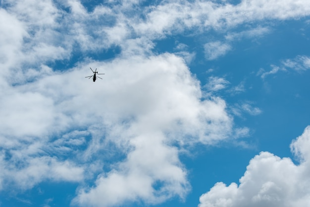 A helicopter flies high against a blue sky with clouds