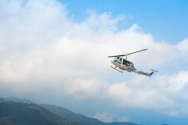 Helicopter in flight, blue sky background