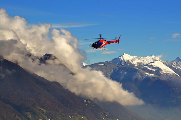 雪をかぶった山々の上の雲の間を飛んでいるヘリコプター