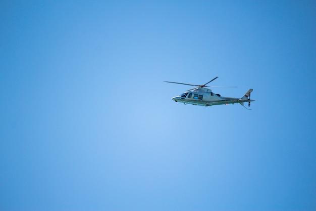 Летание вертолета в голубом небе. синий фон