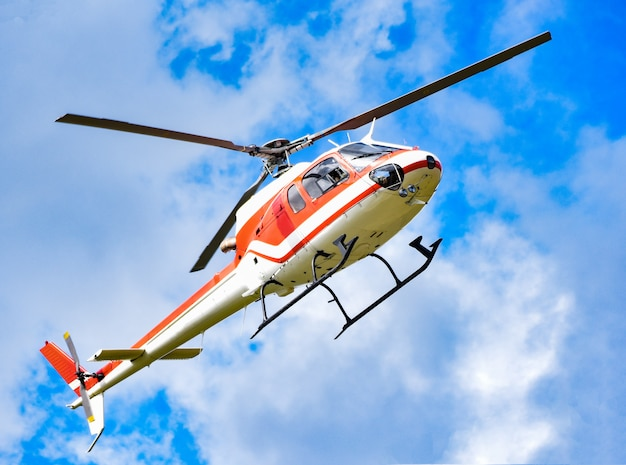 Helicopter flying on sky / white red fly helicopter on blue sky with clouds good air bright day