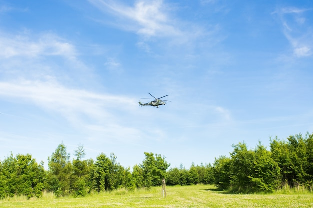 Вертолет летит по синему небу и зеленой земле под ним