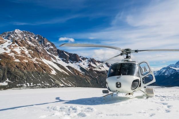 雪の山に着陸するヘリコプター