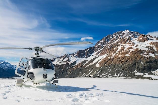 ニュージーランドのクック山にあるタスマン氷河の雪山に上陸するヘリコプター。 Premium写真