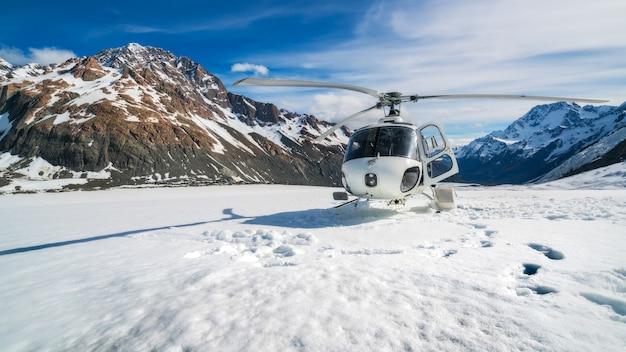 ニュージーランドのクック山にあるタスマン氷河の雪山に上陸するヘリコプター。