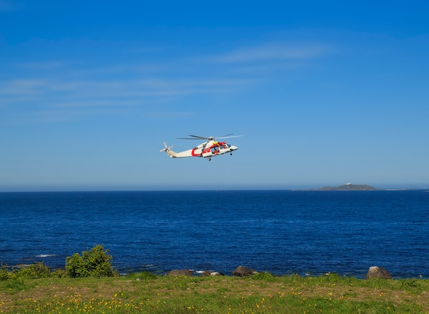 Helicopter over the sea at godoy island near alesund, norway