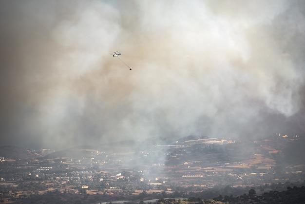 물 양동이가 있는 헬리콥터가 시골 지역에 심한 연기를 날리며 산불과 싸우고 있습니다.