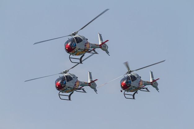 Helicopters of the patrulla aspa taking part in an exhibition on the day of the spanish army forces