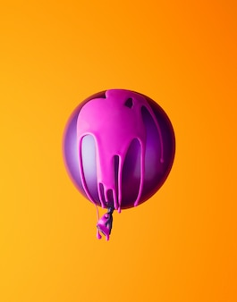 Helium ballon covered in pink paint on orange background