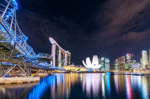 Спиральный мост с заливом марина и центральным деловым районом сингапура в ночное время