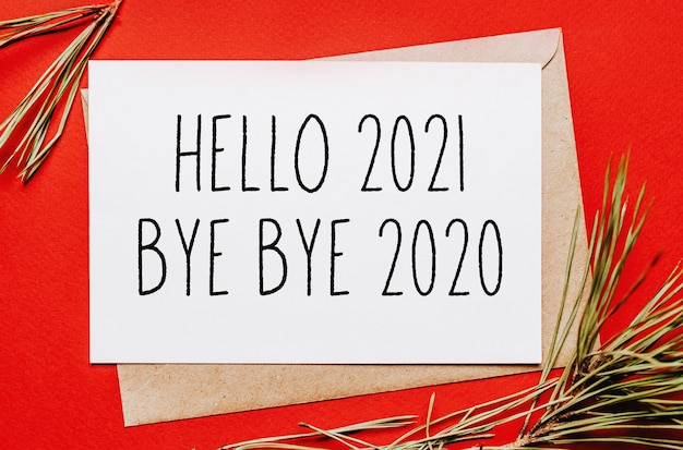 Hello 2021 bye bye 2020 christmas note with fir branch on red isolated wall. new year concept