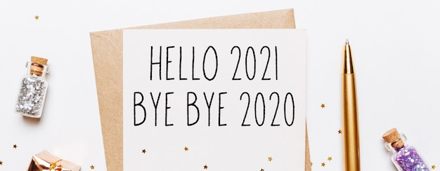 Hello 2021 bye bye 2020 note with envelope, gifts and gold glitter stars on white background. merry christmas and new year concept