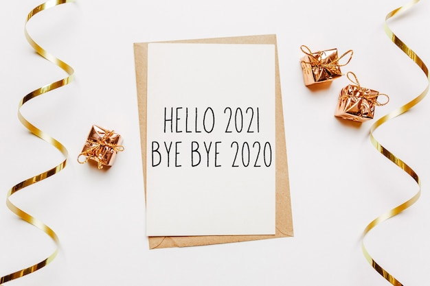 Hello 2021 bye bye 2020 note with envelope, gifts and gold ribbon on white.