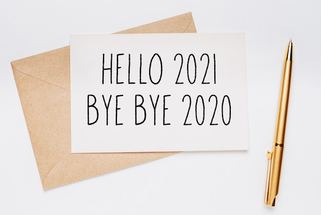 Hello 2021 bye bye 2020 note with envelope and gold pen on white background. merry christmas and new year concept