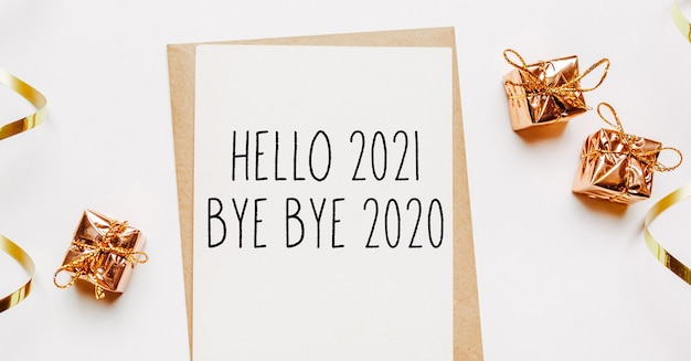 Hello 2021 bye bye 2020 note with gifts and gold ribbon on merry christmas and new year concept