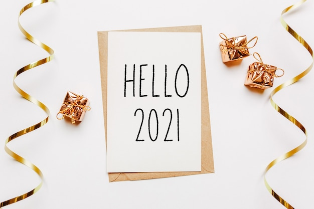 Hello 2021 note with envelope, gifts and gold ribbon on white surface. merry christmas and new year concept