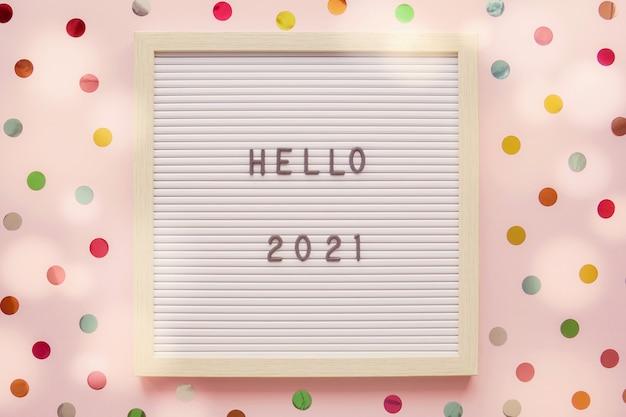 カラフルなドットピンクのパステルカラーの背景を持つレターボード上のhello2021、明けましておめでとうございます