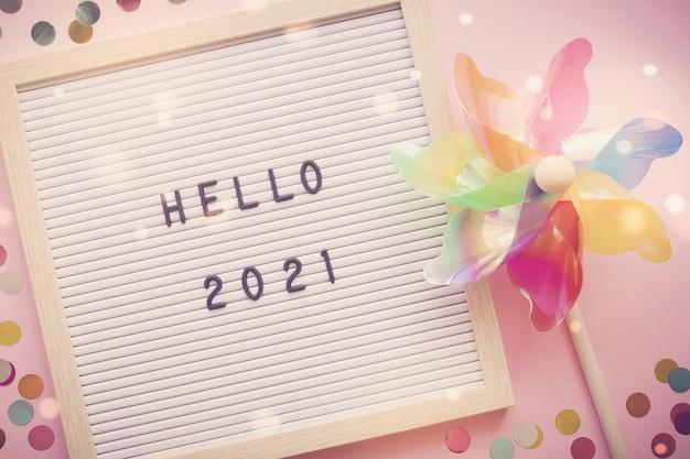 カラフルな風車、新年あけましておめでとうございますのお祝いとレターボード上のhello 2021