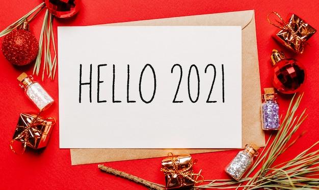 안녕하세요 2021christmas 선물, 전나무 분기와 빨간색 격리 된 배경에 장난감 참고. 새해 개념