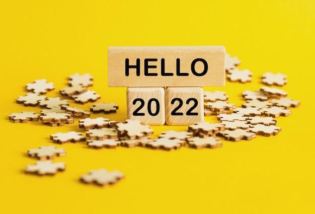 Hello 2022. 노란색 배경에 텍스트가 있는 퍼즐과 나무 큐브. 관리 및 비즈니스에 대한 개념입니다.