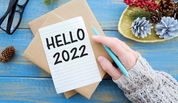 Привет 2022 написано в блокноте на деревянном столе со смартфоном