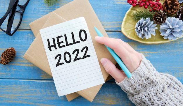 Hello 2022 written in a notebook on wooden desk with smartphone