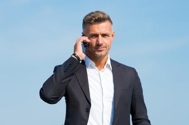 こんにちは、電話に出てください。ビジネスマンは携帯電話で呼び出します。屋外で携帯電話を持つハンサムな男。ビジネスコミュニケーション。業務用電話。 3g。 4g。モバイルライフスタイル。新技術。