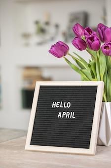 こんにちは4月のレターボードと紫色のチューリップの花の花束