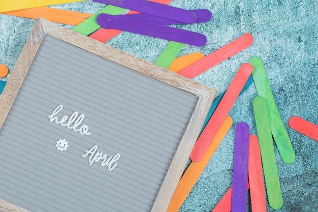 Ciao frase di aprile sulla lavagna grigia con adesivi colorati intorno