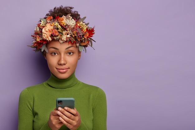 こんにちは秋。緑のカジュアルな服を着て、頭の周りに秋の花輪を持つ愛らしい女性は、携帯電話を使用しています