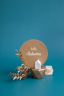 Hello autumn inscription with still life of gold and white decorative elements and leaves on a turqu...